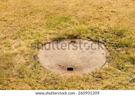 Concrete manhole cover drainage system in the midst of dry cropped grass. - stock photo
