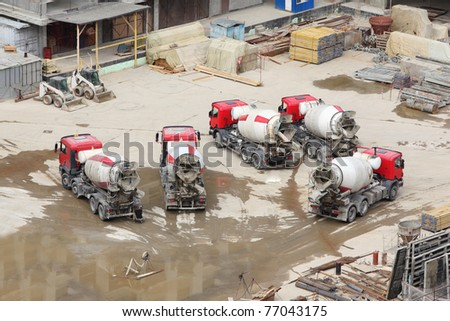 Concrete mixers, tractor and construction materials on big area - stock photo