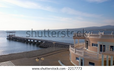 Concrete mooring and the house on seacoast - stock photo