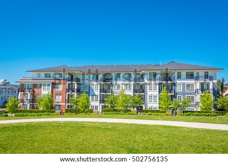 Concrete pathway is crossing green lawn alongside of residential condo building. Apartment building on sunny day with blue sky background