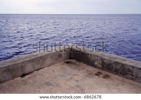 Concrete pier with a view of the ocean.