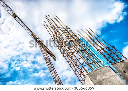 Concrete pillars on industrial construction site. Building of skyscraper with crane, tools and reinforced steel bars - stock photo