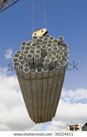 Concrete pipes on the elevating crane - stock photo