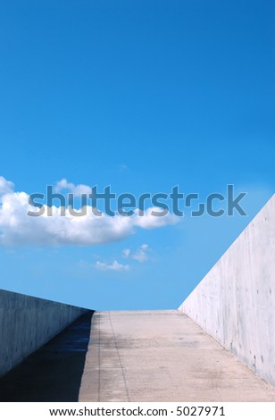 Concrete ramp leading to blue cloudy sky