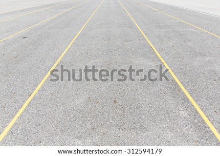 Concrete road texture with yellow color lines, outdoor parking lot, empty street - stock photo