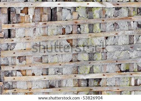 Concrete ruined wall, reinforced wooden lattice - background