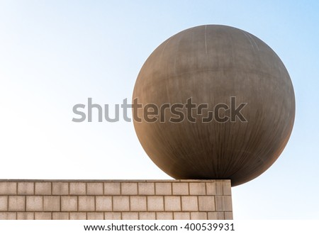 concrete sphere balancing on a rooftop