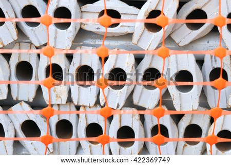 Concrete supporting pillars and pipes under the orange protective mesh - stock photo