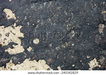 Concrete surface partly covered with black tar.