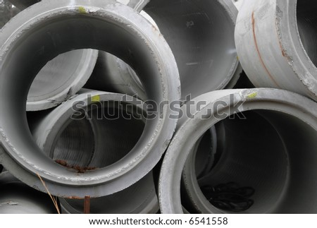 Concrete utility pipes for water, stacked and ready for underground installation.