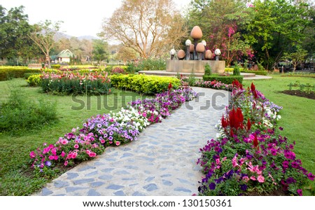 concrete walkway in a lush green park - stock photo