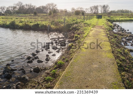 Concrete walkway on a stone pier in the water of a natural pond. - stock photo