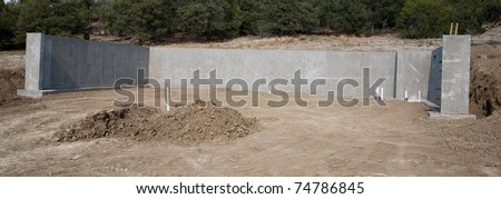 concrete wall and foundation for walk out basement new construction - stock photo