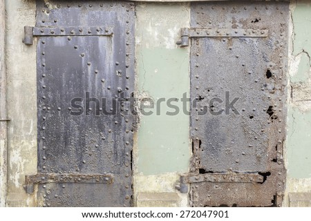 Concrete wall floor background with chips, crack, paint speckles, pale green paint, texture, white paint, steel, rivets, rust, holes, doors - stock photo