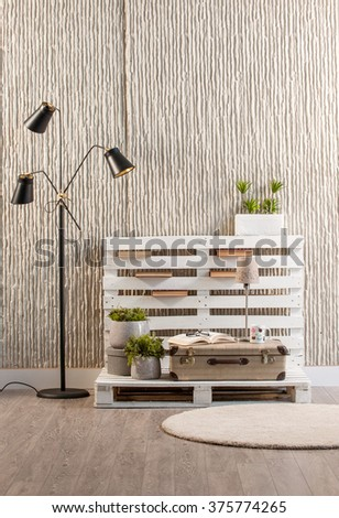 concrete wall interior handmade trendy decor with modern black lamp and round rug - stock photo