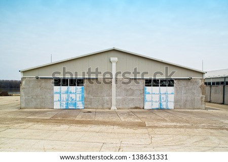 Concrete warehouse exterior with locked metal door - stock photo