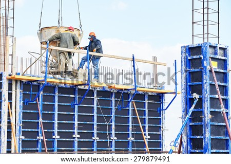 concreting work: construction site workers pouring concrete into formwork at building area with skip - stock photo