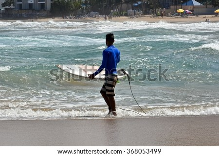CONDADO, PUERTO RICO - JANUARY 26, 2016: A person surfing on Candado Beach in Puerto Rico. Condado Beach is a beach effervescence located at the end of Ashford Avenue in Condado, Puerto Rico.