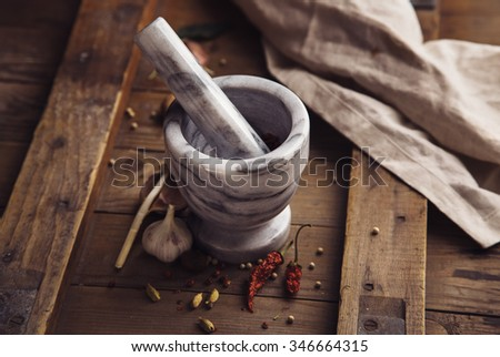 Condiments and Mortar  on a old rustic table. Food background concept - stock photo