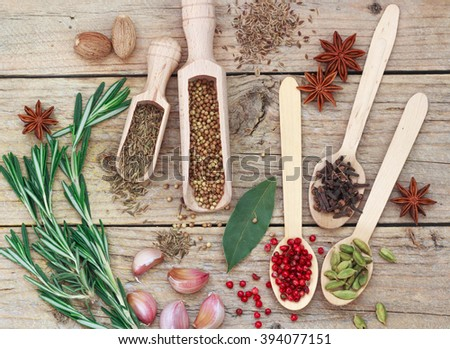 Condiments and spices on the table -  cumin, rosemary, garlic, cardamom, nutmeg, clove Bud, Bay leaf, star anise,  pink pepper,  coriander - stock photo