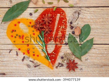 Condiments and spices on the table - turmeric, paprika, cumin, rosemary, cardamom, nutmeg, clove Bud, Bay leaf, star anise, green and pink pepper, juniper, coriander - stock photo