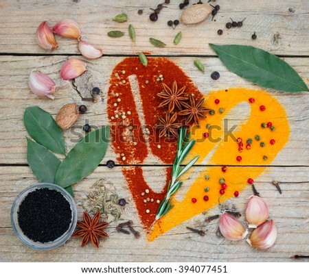 Condiments and spices on the table - turmeric, paprika, cumin, rosemary, garlic, cardamom, nutmeg, clove Bud, Bay leaf, star anise, green and pink pepper, juniper, coriander, Nigella - stock photo