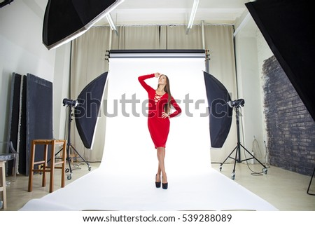 Conditions of work in the studio, a professional model in red dress posing in photo studio