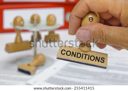 conditions printed on rubber stamp in hand - stock photo