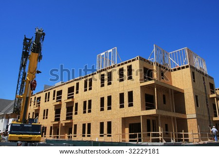 Condo community under construction with crane - stock photo