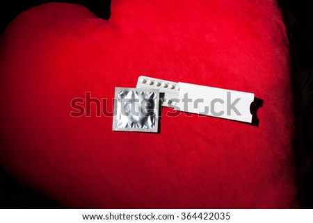 Condom and birth control pills, on red textile background - stock photo