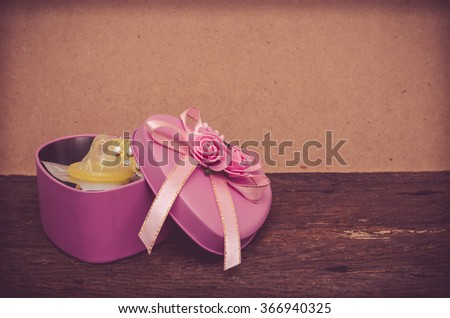 Condom and contraceptive pill in heart shape box - stock photo