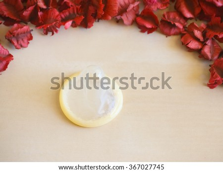 Condom and dry flower background. - stock photo