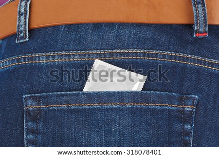 Condom in jeans pocket - health background - stock photo