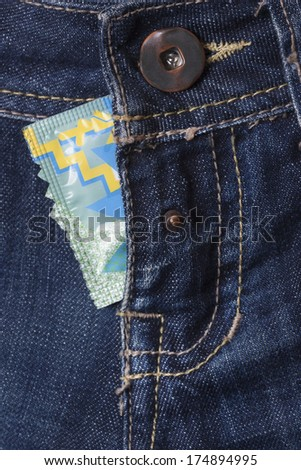 Condom in the blue jeans  - stock photo