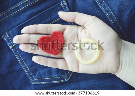 Condom in woman's hand.safe sex, AIDS.Remember about protection!