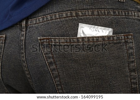 Condom inside pocket of man pants. Contraceptive concept - stock photo