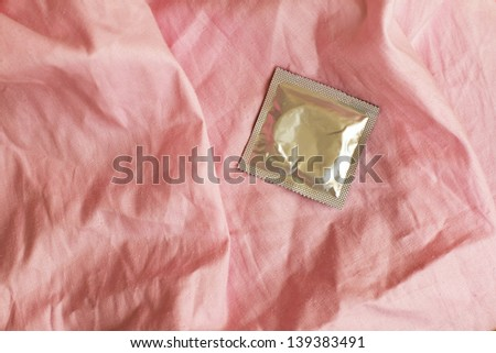Condom on crumpled the pink bedsheet - stock photo