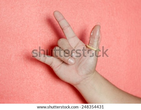 condom on hand on pink background,safety sex concept - stock photo