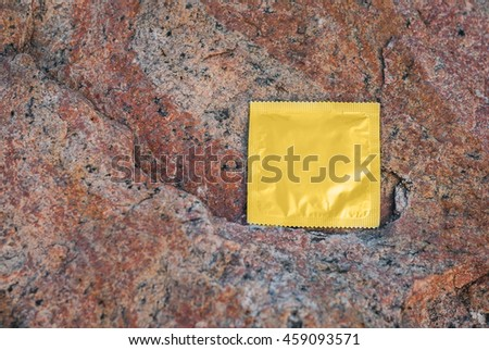 Condom surface. Gold condom lying on a rock - stock photo