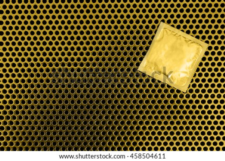 Condom surface. Gold condom lying on gold metal - stock photo