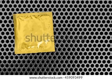 Condom surface. Gold condom lying on metal - stock photo