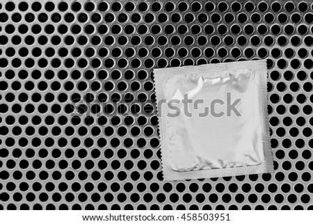 Condom surface. Silver condom lying on metal - stock photo