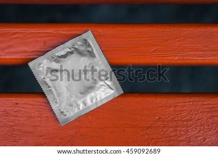 Condom surface. Silver condom lying on the orange bench - stock photo