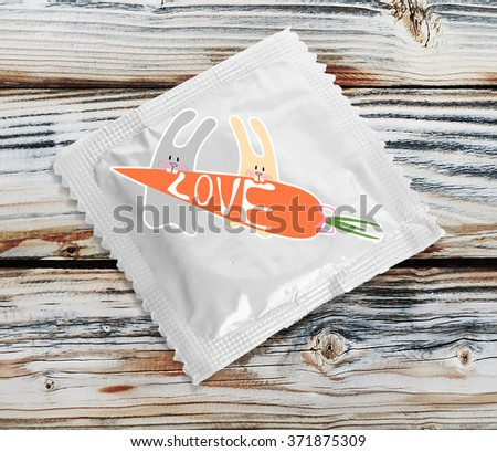 Condom with pictures on wooden table - stock photo