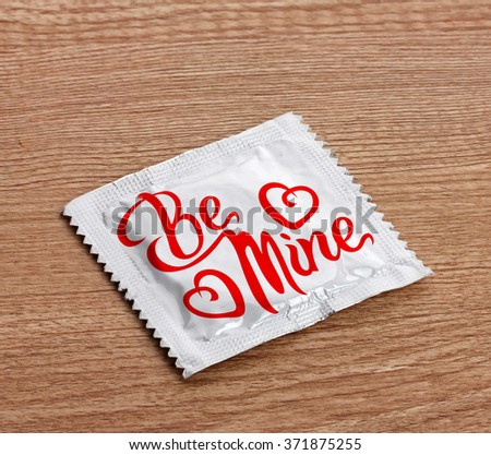 Condom with text Be mine on wooden table - stock photo