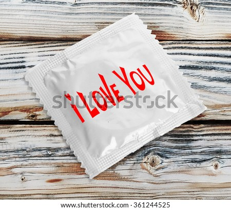 Condom with text I love you on wooden table - stock photo