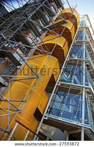 Condominium under construction with yellow stairs - stock photo