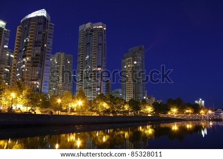 Condominiums at twilight reflecting in the calm water of Coal Harbor in downtown vancouver. British Columbia, Canada. - stock photo