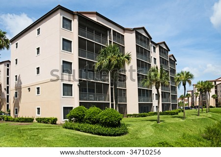 Condominiums surrounded by palm trees and blue sky background - stock photo