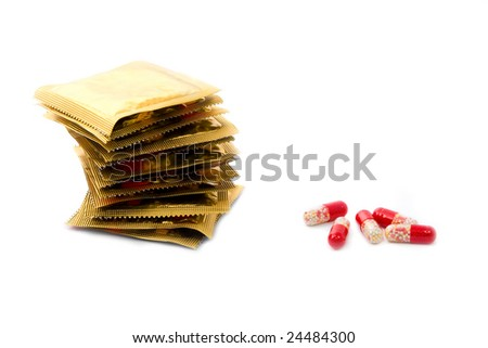 Condoms in a stack and oral contraceptive pills isolated on white - stock photo